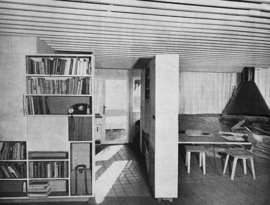 Looking into the kitchen with a fixed storage unit on the left. The central storage unit is hinged at the rear column with a fixed castor at the nearest end, enabling the wall to be moved left or right to maximise spaces as and when needed. The dining table is hinged at the left end and folds up into the storage wall, enabling the fireplace area to be more fully used after dinner. The curtains pull to the left revealing a stone wall behind and the large glazed wall to the right and north which lets the sun in. The glass runs right down into the soil without any sill, enhancing the continuity of indoor space with the outdoors. The original metal hood has yet to receive its render coating as in the other photo.